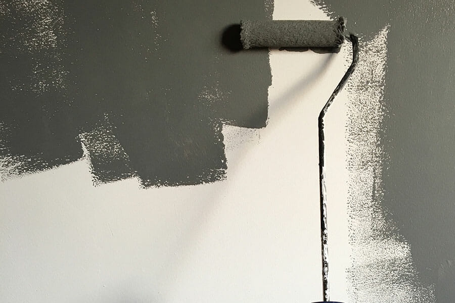 Person holding paint-roller while painting the wall
