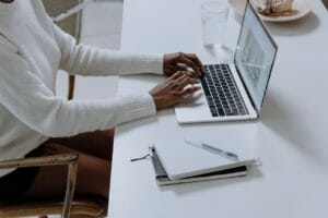A person in a white sweater using a laptop