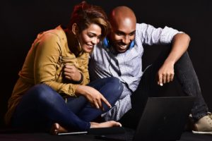 A happy couple looking at a laptop.