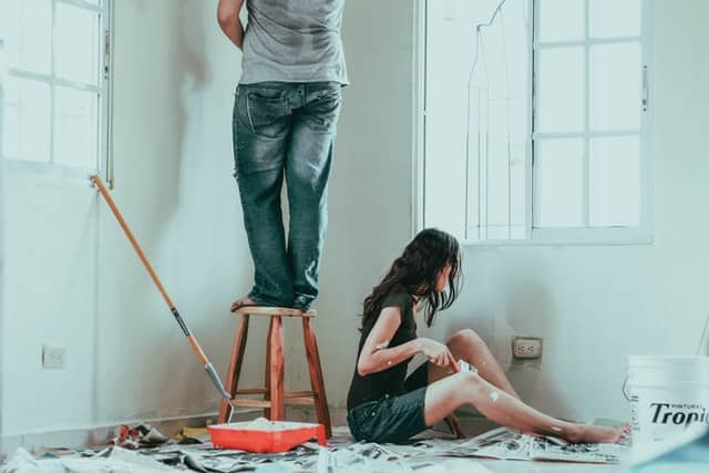 Couple painting house walls white.