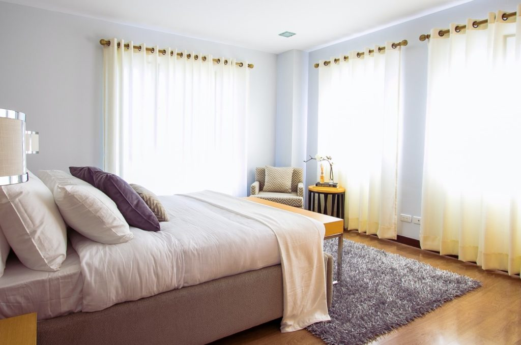 bedroom with bed and windows and curtains
