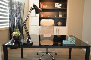 A home office equipped with a desk, a chair, and some shelving
